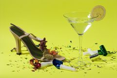 Party is over. Martini drink, fancy shoe and party blowers over green background Royalty Free Stock Images