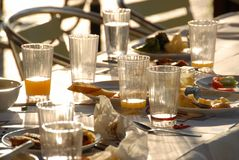 The party is over. Leftover of food and drink on a restaurant table outside Royalty Free Stock Photo
