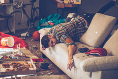 When the party is over. Young handsome man passed out on sofa in messy room after party Royalty Free Stock Images