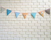 Party pastel color flag strips on the wall (medium shot). Party pastel color flag strips on the white brick block wall (medium shot Royalty Free Stock Image