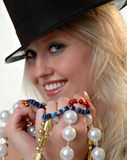 Party Pearls. A girl in a party hat with jewelry in her hands Stock Image