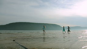 Party and people concept - group of smiling teen girls jumping on beach. Silhouette of three young women running around stock footage