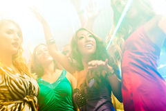 Party people dancing in disco or club. Group of party people - men and women - dancing in a disco club to the music Stock Image