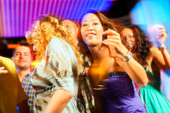 Party people dancing in disco or club. Group of party people - men and women - dancing in a disco club to the music Royalty Free Stock Images