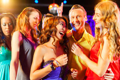 Party people dancing in disco or club. Group of party people - a men and women - dancing in a disco club to the music Royalty Free Stock Photos