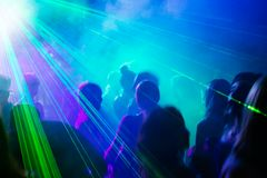 Party people dancing under laser light. Crowd of people dancing under disco laser light Stock Photo