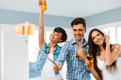 Party People. Friends Making Photo With Smartphone Selfie-stick. Royalty Free Stock Image