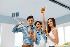 Party People. Friends Making Photo With Smartphone Selfie-stick. Royalty Free Stock Photography