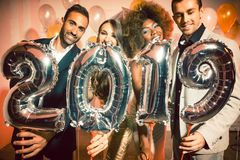 Party people women and men celebrating new years eve 2019. With sparklers and Champagne stock photography