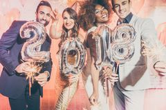 Party people women and men celebrating new years eve 2018. With sparklers and Champagne Stock Photo