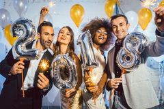 Party people women and men celebrating new years eve 2018. With sparklers and Champagne royalty free stock image