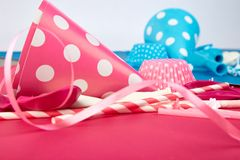 Party pink and blue paper hat. Celebration. Party pink and blue hat polka dot background. Birthday paper hat, candles, tubes and balloons stock image