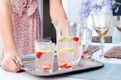 Party planner bringing water to the table Royalty Free Stock Image