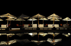 Parasols by the Pool at Night Royalty Free Stock Photos
