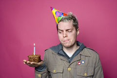 Party pooper. Birthday boy disappopinted with his cupcake and candle Stock Image