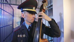 A party in the prison cell. A policeman in uniform plays the double bass. Female officers and the homeless dance in the background. Slow motion stock video