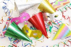 Party props. Party cone caps, streamers, pipes and carnival masks shot from above stock photos
