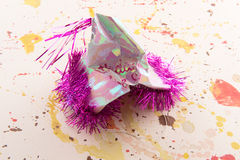 The Party's Over. Concept photo of crumpled birthday party hat on paint splattered background for the idea that the party is over royalty free stock photography