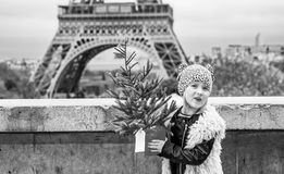 Girl with Christmas tree in front of Eiffel tower in Paris. The Party Season in Paris. Full length portrait of cheerful modern girl with Christmas tree in the Royalty Free Stock Photo