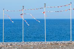 Party or season of vacations is over - an empty sea beach with pillars for festive flags. Stock Images