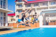 Party at smimming pool. Group of cheerful friends jumping into water. Youth and carefree concept Royalty Free Stock Images