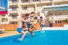 Party at smimming pool. Group of cheerful friends jumping into water. royalty free stock photography