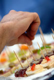 Party snack. A hand picks from a selection of party canapes Royalty Free Stock Photography