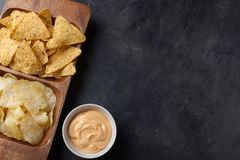 Party snack, chips, Nacho with cheese sauce in a wooden plate on the dark concrete table. top view, copy space Stock Images