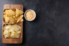 Party snack, chips, Nacho with cheese sauce in a wooden plate on the dark concrete table. top view, copy space Stock Image