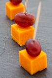 Party snacks. Cheese cubes and grapes Royalty Free Stock Photos