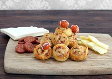 Sliced pepperoni, cheddar cheese and pepperoni pinwheels decorat. Party snacks of sliced pepperoni, cheddar cheese and pepperoni pinwheels.  Decorated with Stock Photo