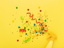 Party spray concept on yellow background. Party spray on yellow background. Bright creative background with explosion of serpentine, confetti and candies Royalty Free Stock Photos