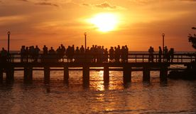 Party at Sunset. A group of people standing on a pier at sunset royalty free stock image