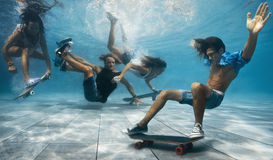 Party in the swimming pool. Men and Women skateboarding underwater in the swimming pool Stock Images