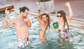 Party in the swimming pool. Three friends drinking and dancing on the roof top pool Royalty Free Stock Photography