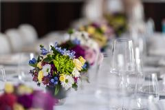 Party table with glasses and flowers stock images