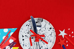 Party table setting background. Party and celebration table setting on red table cloth background Stock Photo