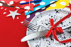 Party table setting. Party and celebration table setting on red table cloth background Royalty Free Stock Photo