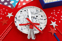 Party table setting with decoration. Party and celebration table setting with gift box on red table cloth background Stock Photography