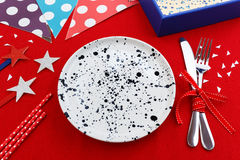 Party table setting with party decoration. Party and celebration table setting with gift box on red table cloth background Royalty Free Stock Image