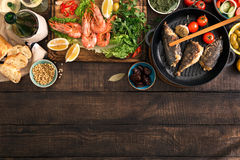 Party table with shrimp, fish grilled, salad, snacks, white wine Stock Images