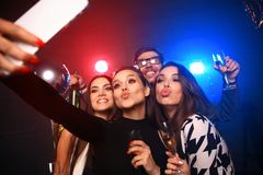 Party, technology, nightlife and people concept - smiling friends with smartphone taking selfie in club. Party, technology, nightlife and people concept royalty free stock image