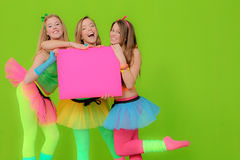 Party teens holding board. Fashion girls in neon clothing holding blank pink billboard board or poster Royalty Free Stock Photos