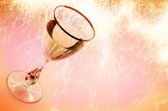 Party theme. Picture of a glass with liquid inside and with a flame on the background Stock Photo
