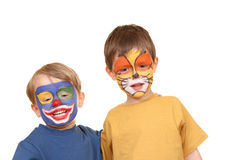 Party time. Five and three years old boys with painted faces isolated on white Royalty Free Stock Photography