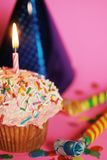 Party time. A small pink cupcake with shinny hat and noisemakers on pink background Stock Photos