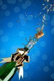 Party time. Champagne splashes from bottle and popping cork on blue background stock photo