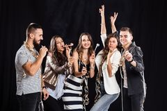 Party time. Company of friends in fashionable casual clothes rejoice and have fun on a black background in the studio royalty free stock photo