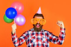 Party time. Joy, fun and happiness concept. Happy Man with balloons. Bearded man in party cap and big glasses.