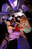 Party time in limousine. With elegant young girls and chauffeur, drinking champagne Stock Images